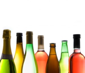Different styles of wine and beer in their bottles, backlit, copy space